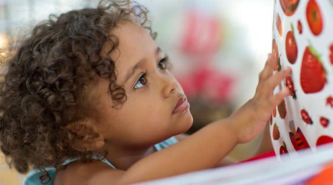 toddler looking through a book