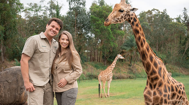 Pregnant Bindi Irwin with her husband Chandler and a giraffe in the background at the zoo.