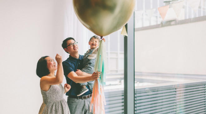 couple about to pop balloon to release the gender of their baby