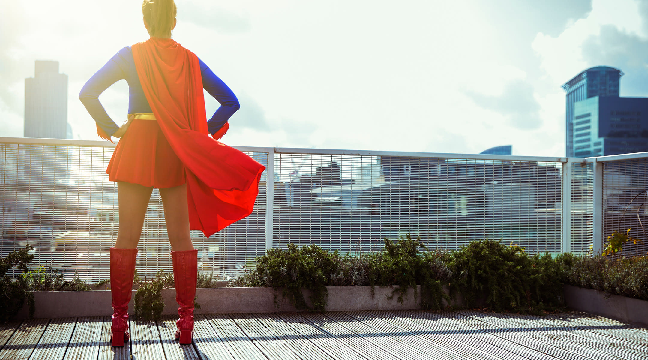 superhero mom standing on balcony with red cape
