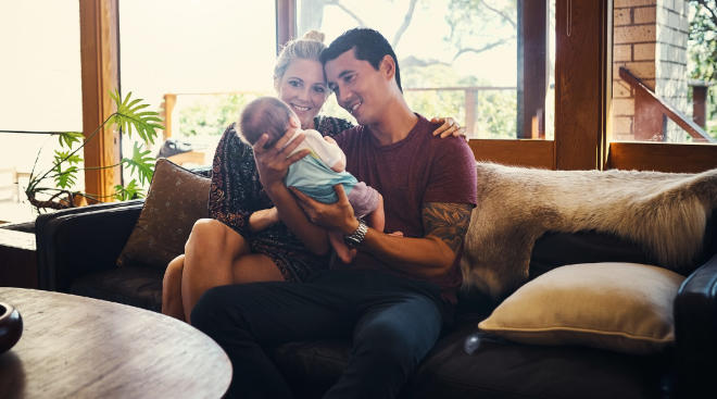 new parents happily holding their newborn baby