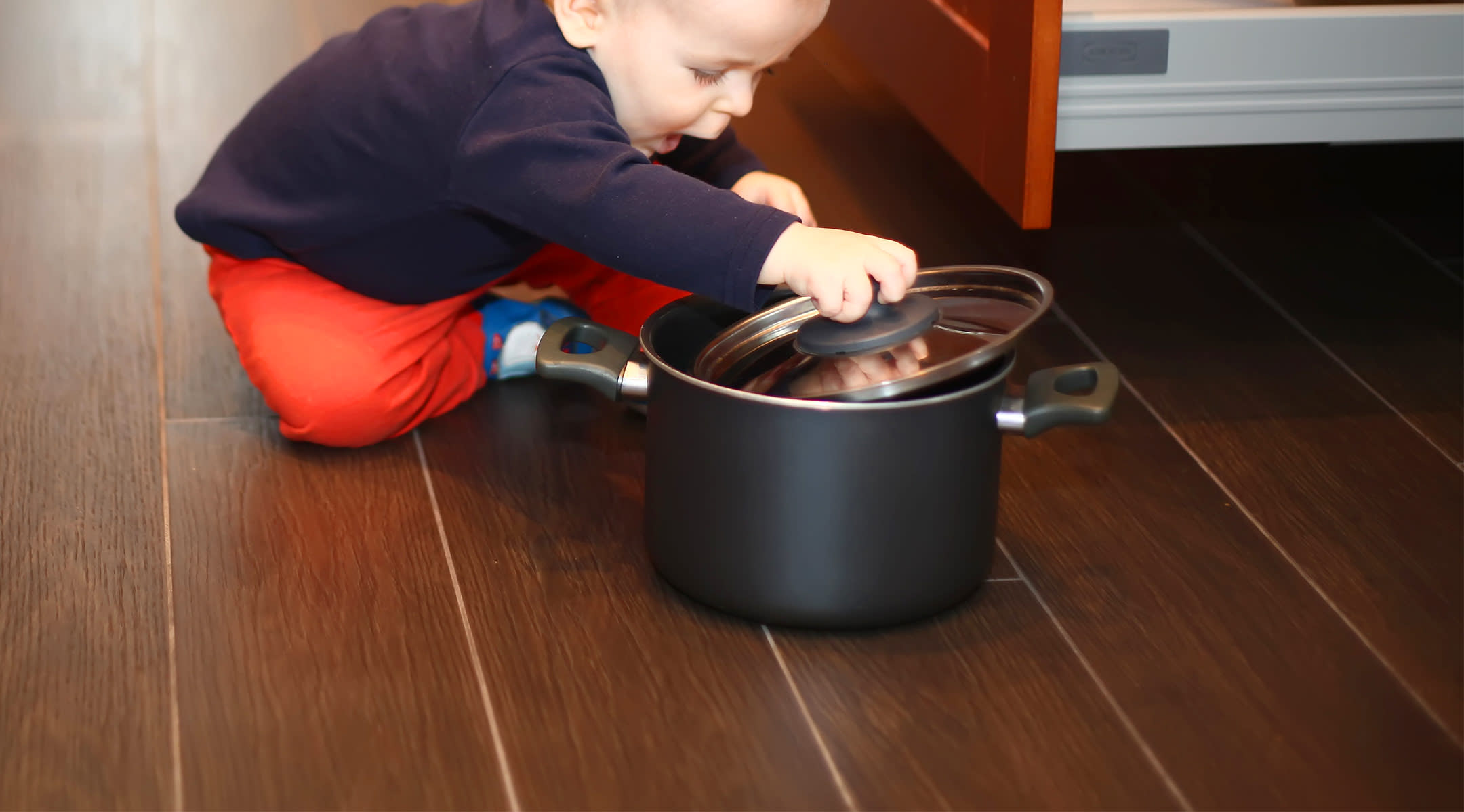 baby playing with pot on kitchen floor