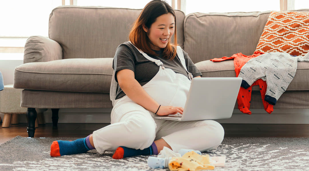 very pregnant woman looking at her laptop