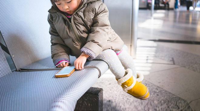 toddler girl using mobile phone at the airport