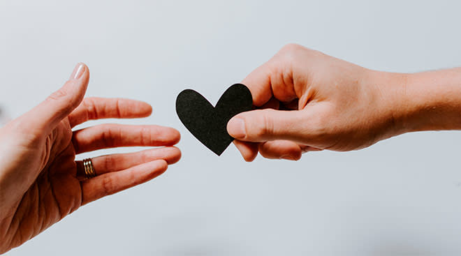two hands passing a paper heart between them