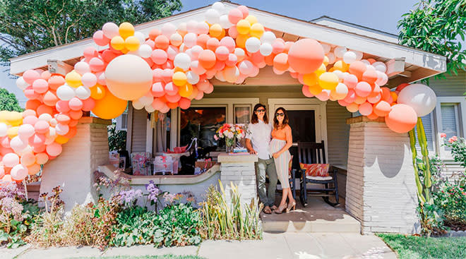 couple throws walk by baby shower, the front of their house decorated with lots of balloons
