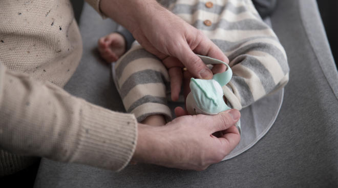 Adult securing Owlet Smart Sock on baby's foot