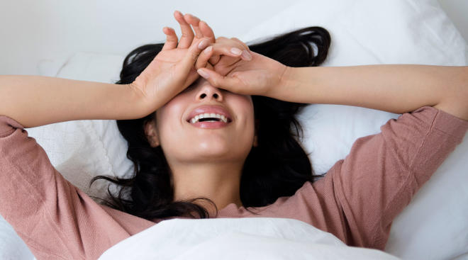 woman in bed covering her face and laughing