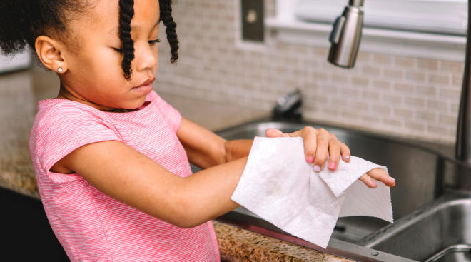 little girl drying her hands after washing them in the kitchen