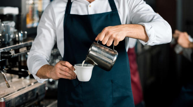 male barista in coffee shop pouring milk into cup