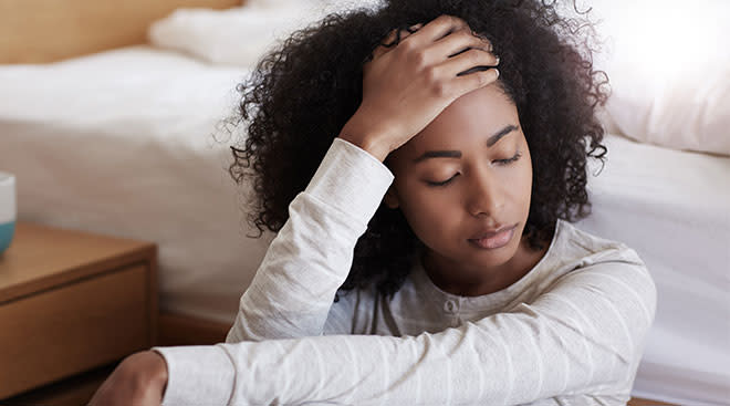 frustrated woman sitting by bed with her hand touching her forehead