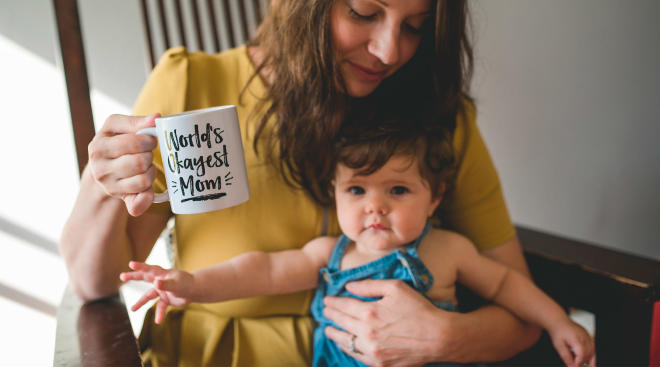 """mom holding baby with mug that says, """"world's okayest mom"""" speaking to the idea of mom shaming"""