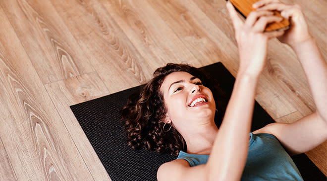 Woman laughing and getting ready to exercise while looking at her phone.