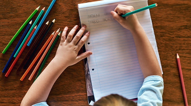 child's hands writing on notebook paper