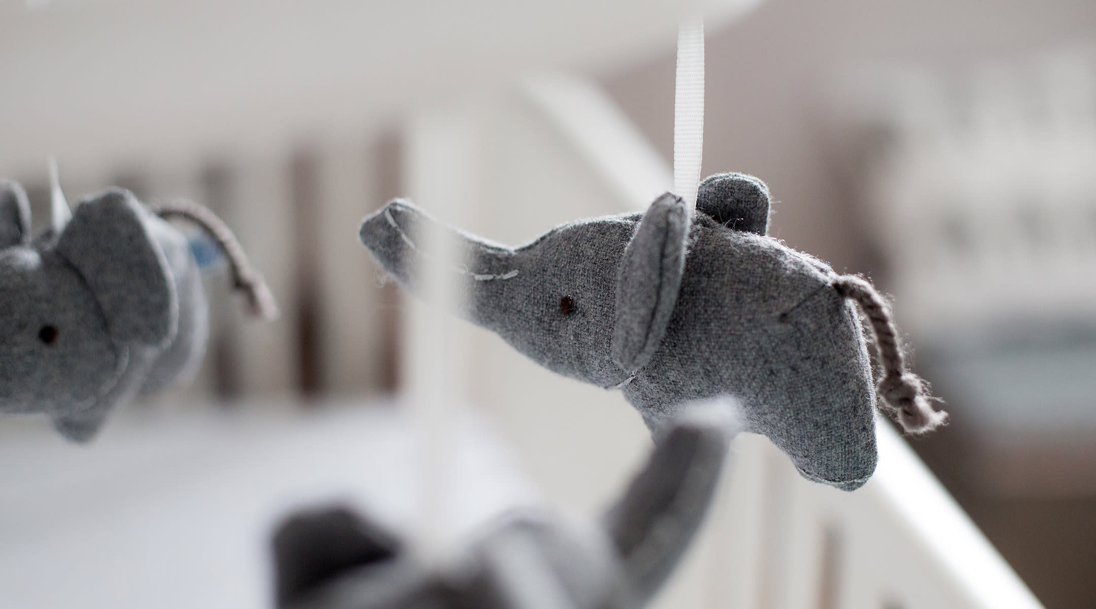 Closeup of an elephant hanging on a mobile above a crib