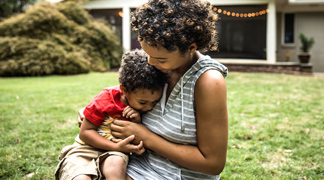 mom hugging her toddler son in yard in front of their house