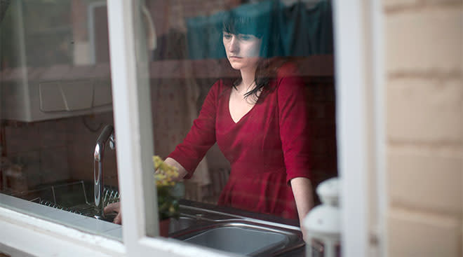 nervous woman stands by window