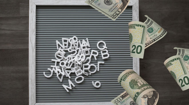 letterboard with pile of mixed up letters and twenty dollar bills