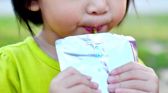 toddler drinking from juice pouch