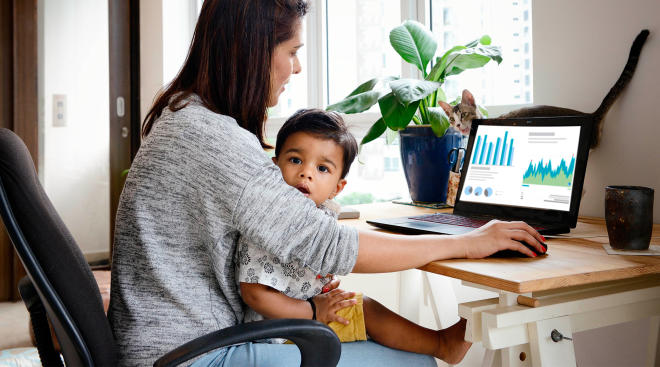 mom working with toddler on her lap