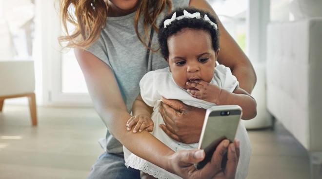 happy mom taking phone photo of baby