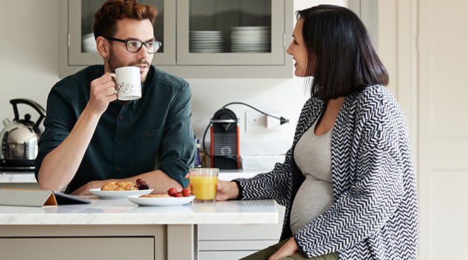 Pregnant woman in the kitchen with her partner eating a healthy breakfast.