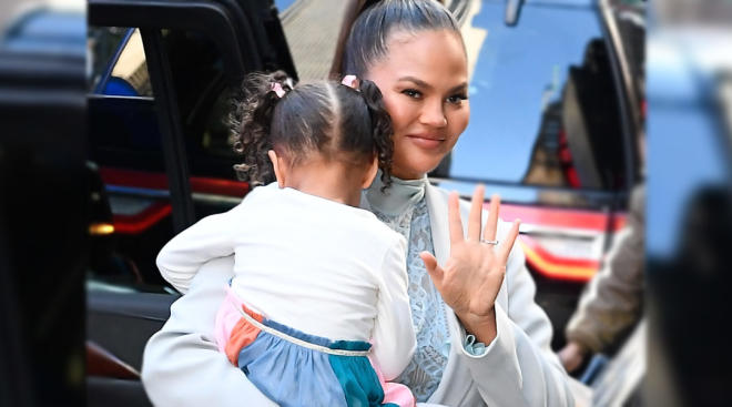 chrissy teigen holding her daughter, who is hiding her face