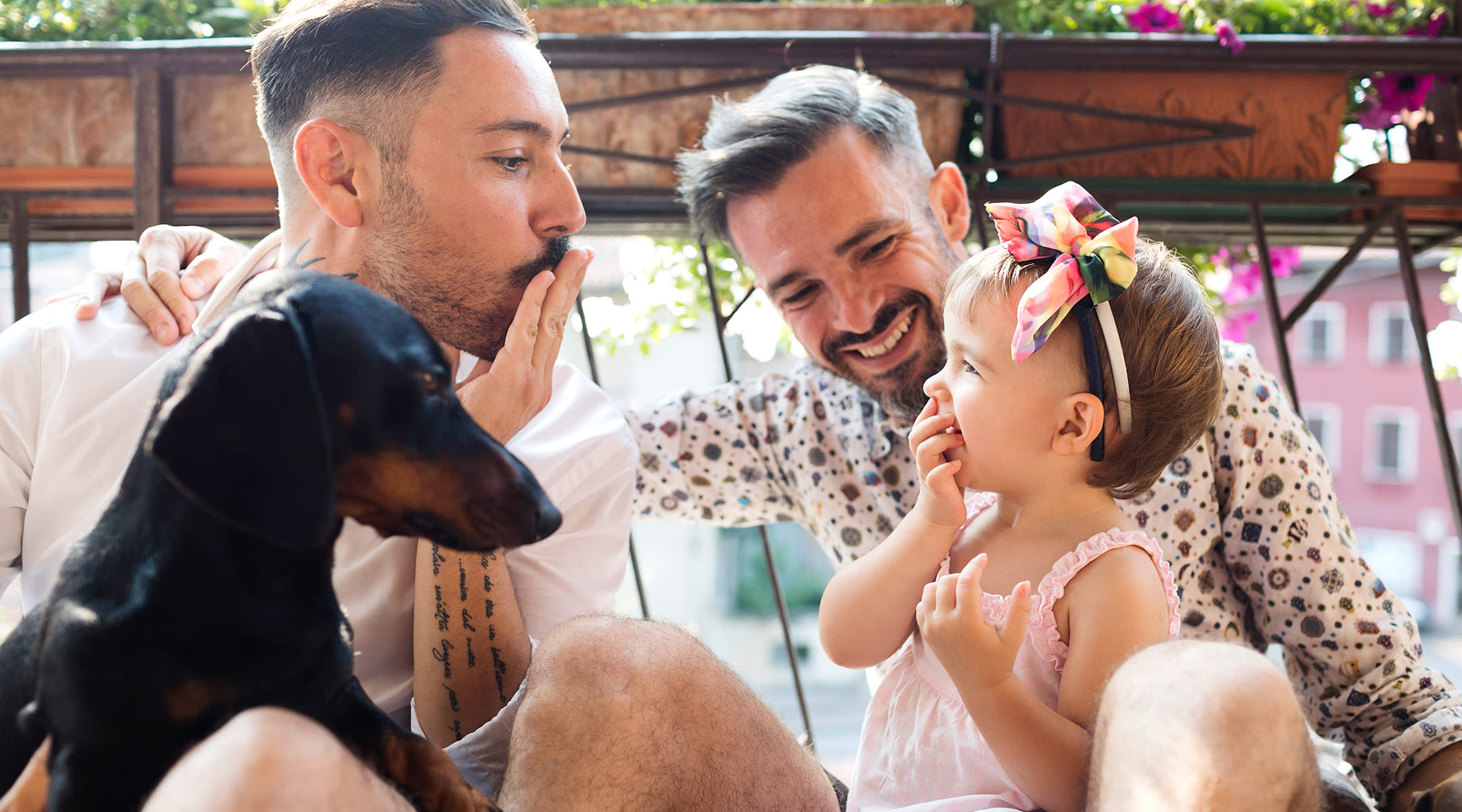 Baby girl wearing headband bow, laughing with her dads