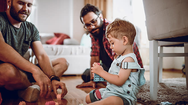 two dads playing with baby boy
