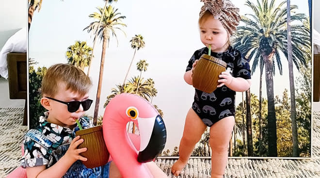 two toddlers against fake palm tree vacation backdrop
