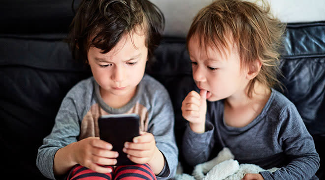 two toddlers play with iphone