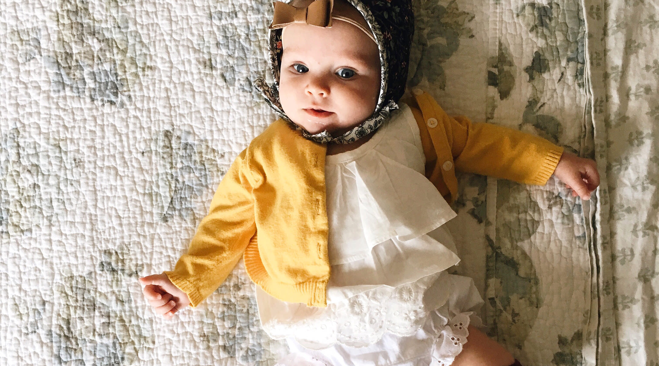 baby dressed in pretty bonnet, with gold bow and cute socks