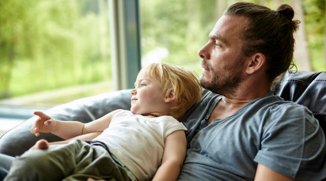 dad holding young son looks out of window