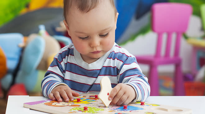 Toddler playing with wooden peg puzzle