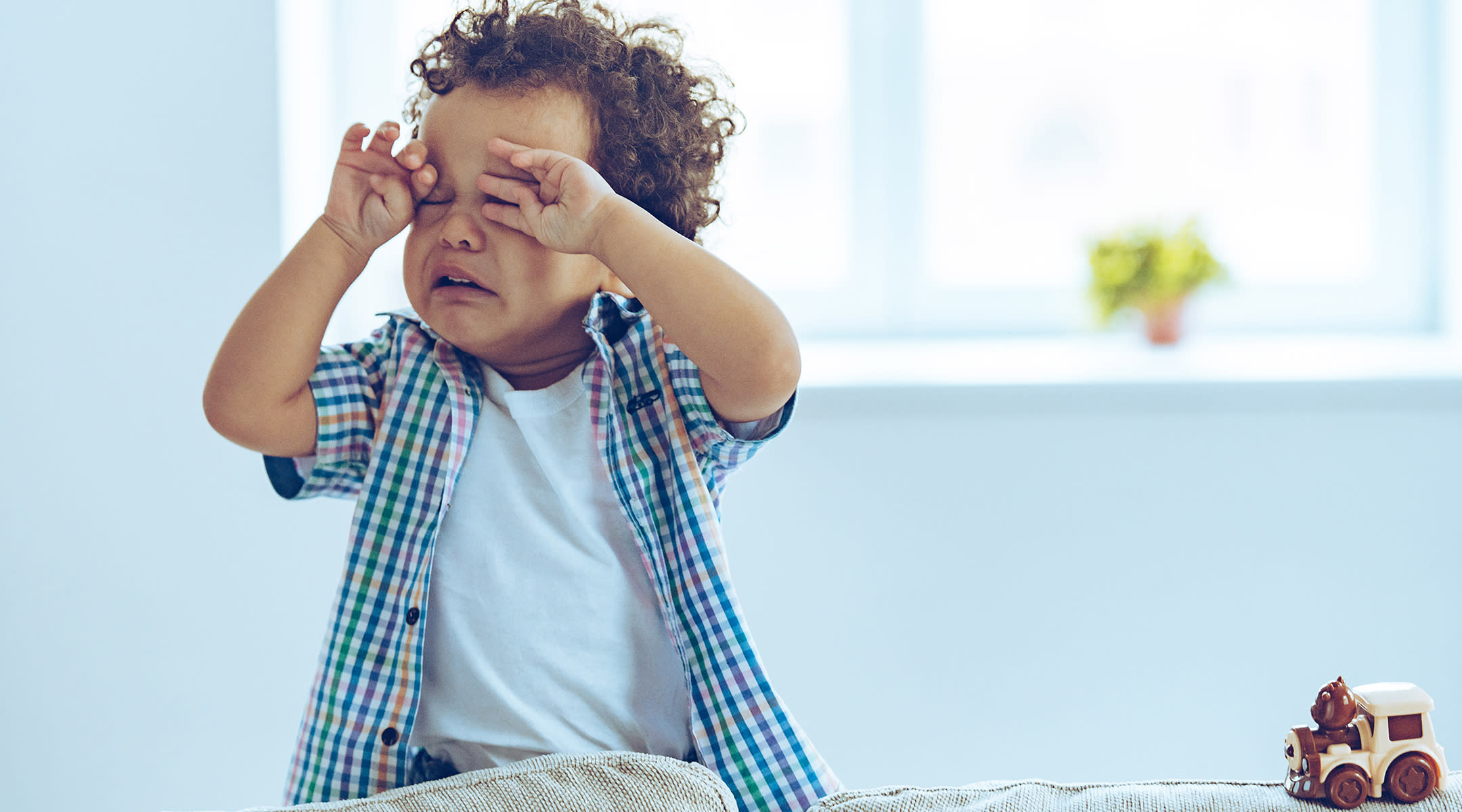 toddler sitting on couch rubbing his eyes and crying