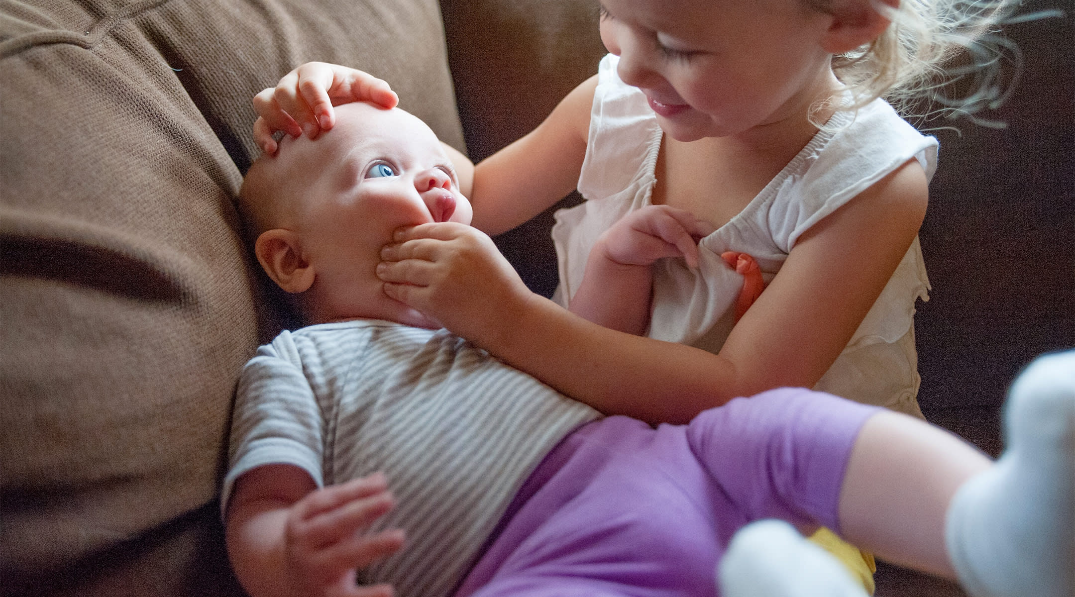 toddler with her baby sister, squishing her face