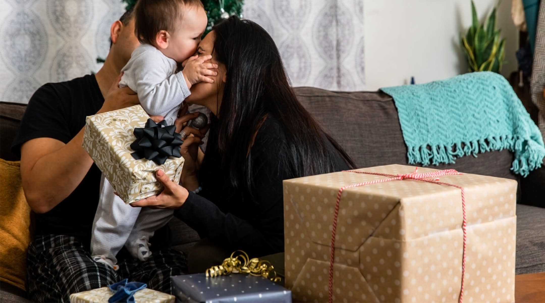 parents hugging baby on christmas morning with gifts nearby
