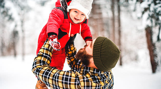 dad lifting up his baby, wearing a red snowsuit in winter