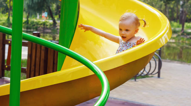 little girl sliding down slide at playground