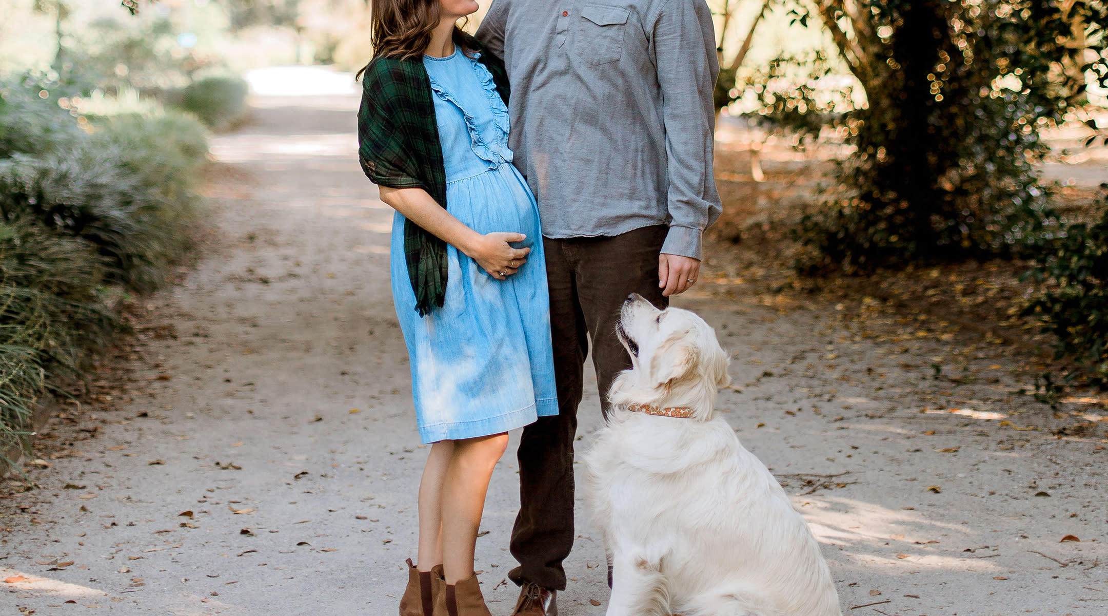 pregnant couple walking outside with pet dog