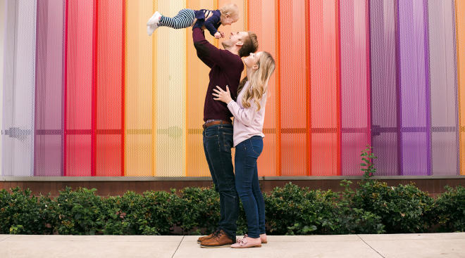 parents holding up baby in front of colorful background