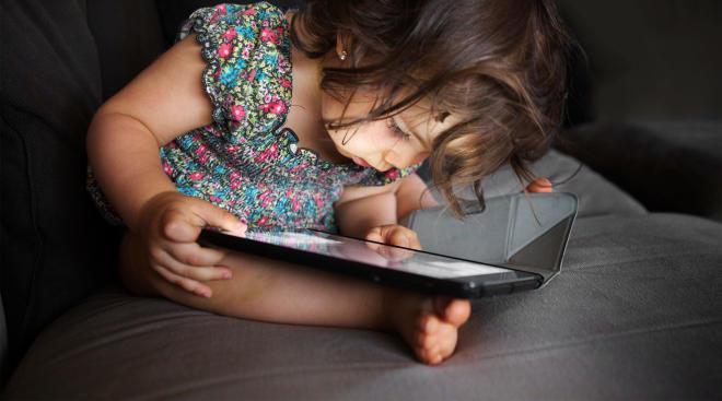toddler staring at tablet