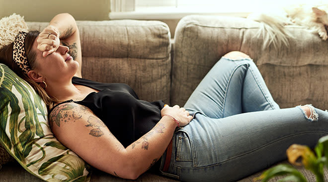 Woman resting at home on the couch recovering from c-section.