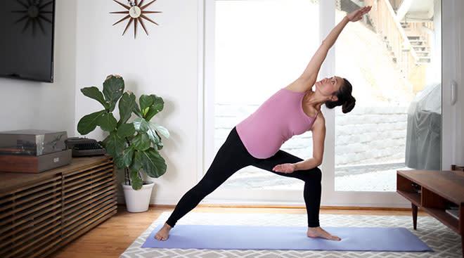 Pregnant woman exercising and doing yoga in maternity leggings.