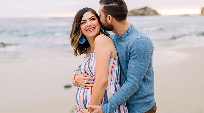 pregnant woman in maxi dress on the beach with her partner