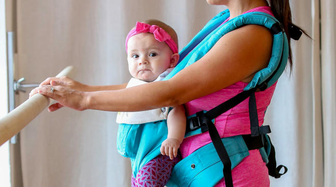 mom wearing baby in carrier while exercising