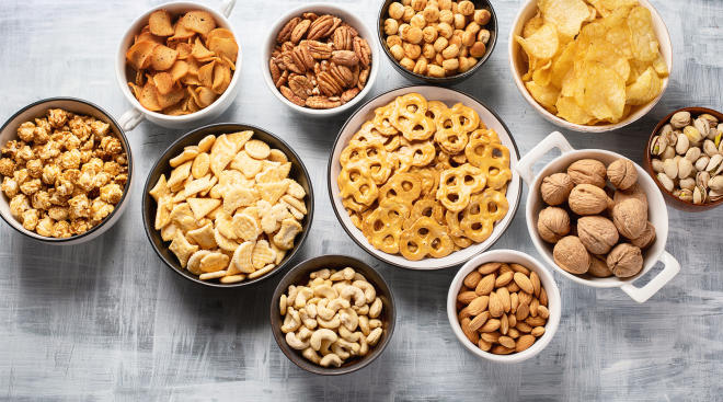 various types of snacks including nuts arranged in bowls