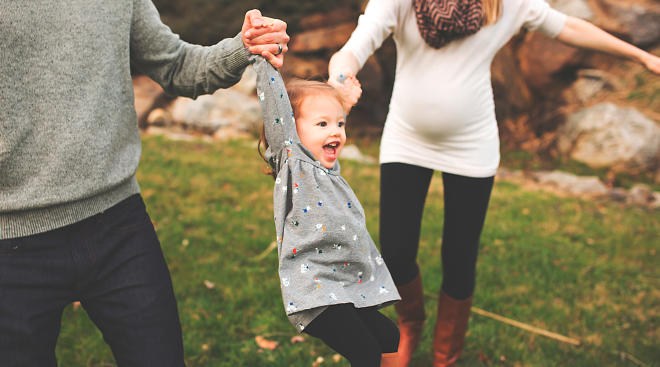 parents lifting happy little girl into the air