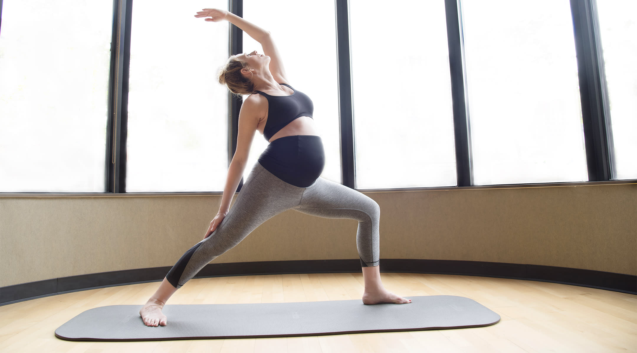 pregnant woman doing yoga in maternity fitness clothes