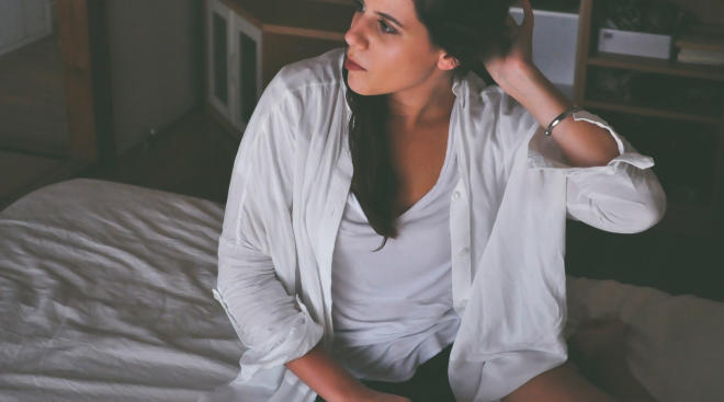 sad woman with sore nipples sitting on bed